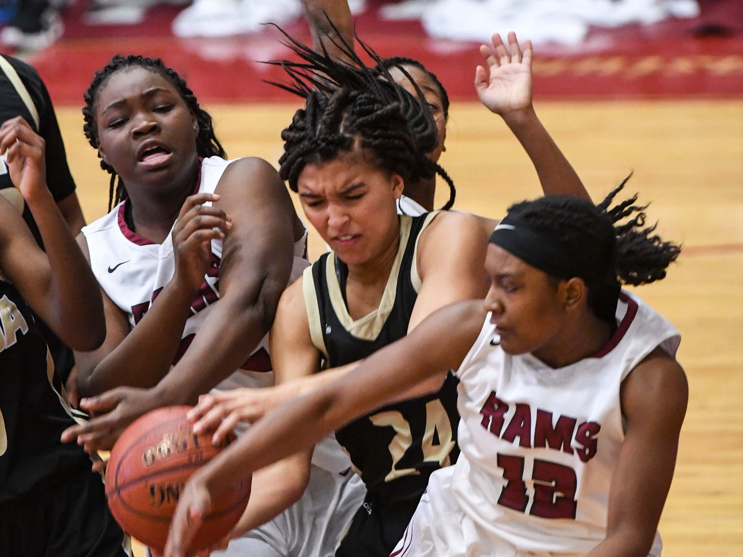 TL Hanna junior Maleia Bracone(24) rebounds around Westside sophomore Chyna Dixon(22) and Westside freshman Branya Pruitt(12) during the first quarter at Westside High School in Anderson on Friday.