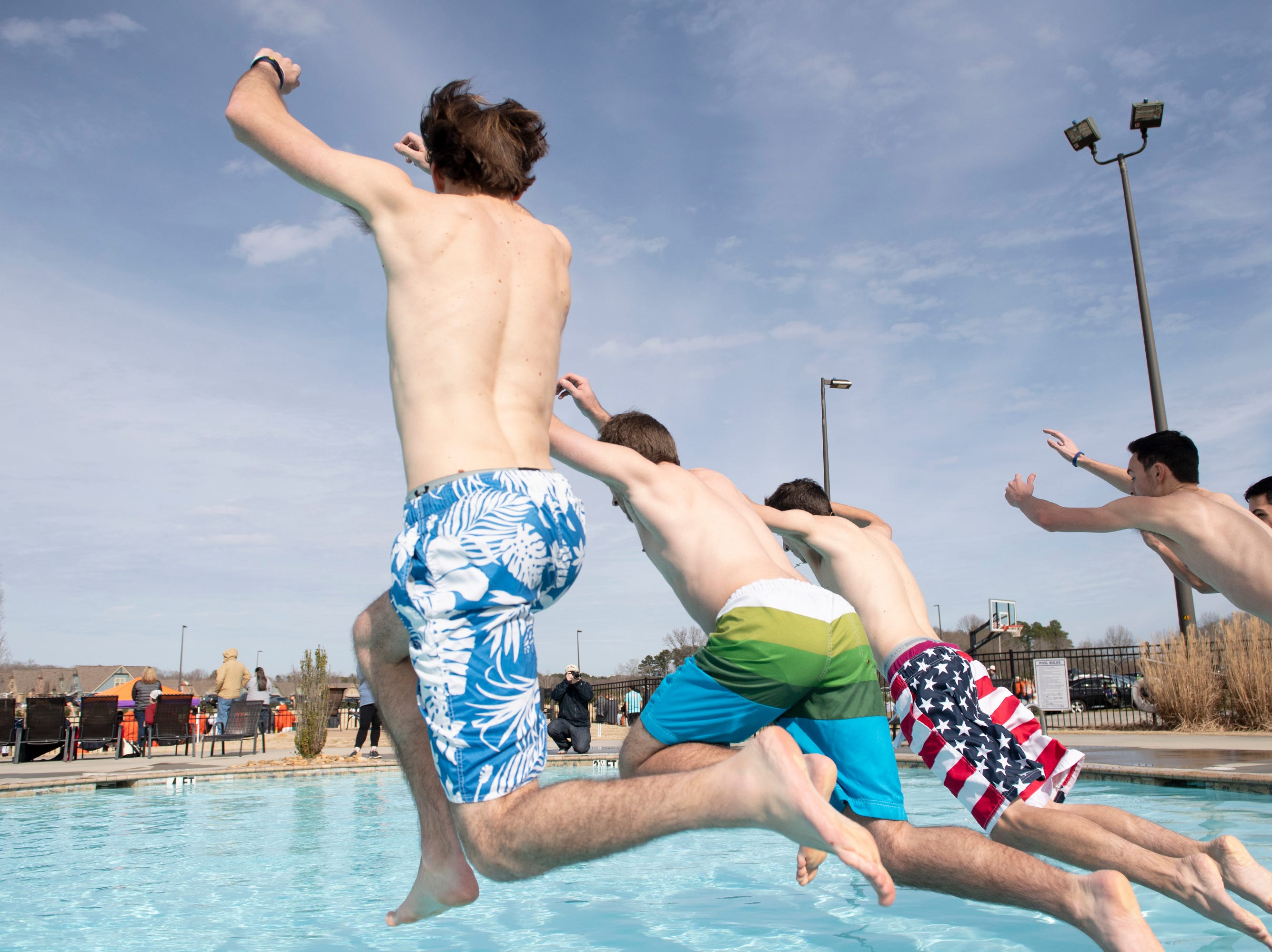 Participants in the 2019 Tiger Paw Polar Plunge jump into the cold pool at The Pier housing complex in Seneca Saturday, Feb. 9, 2019.