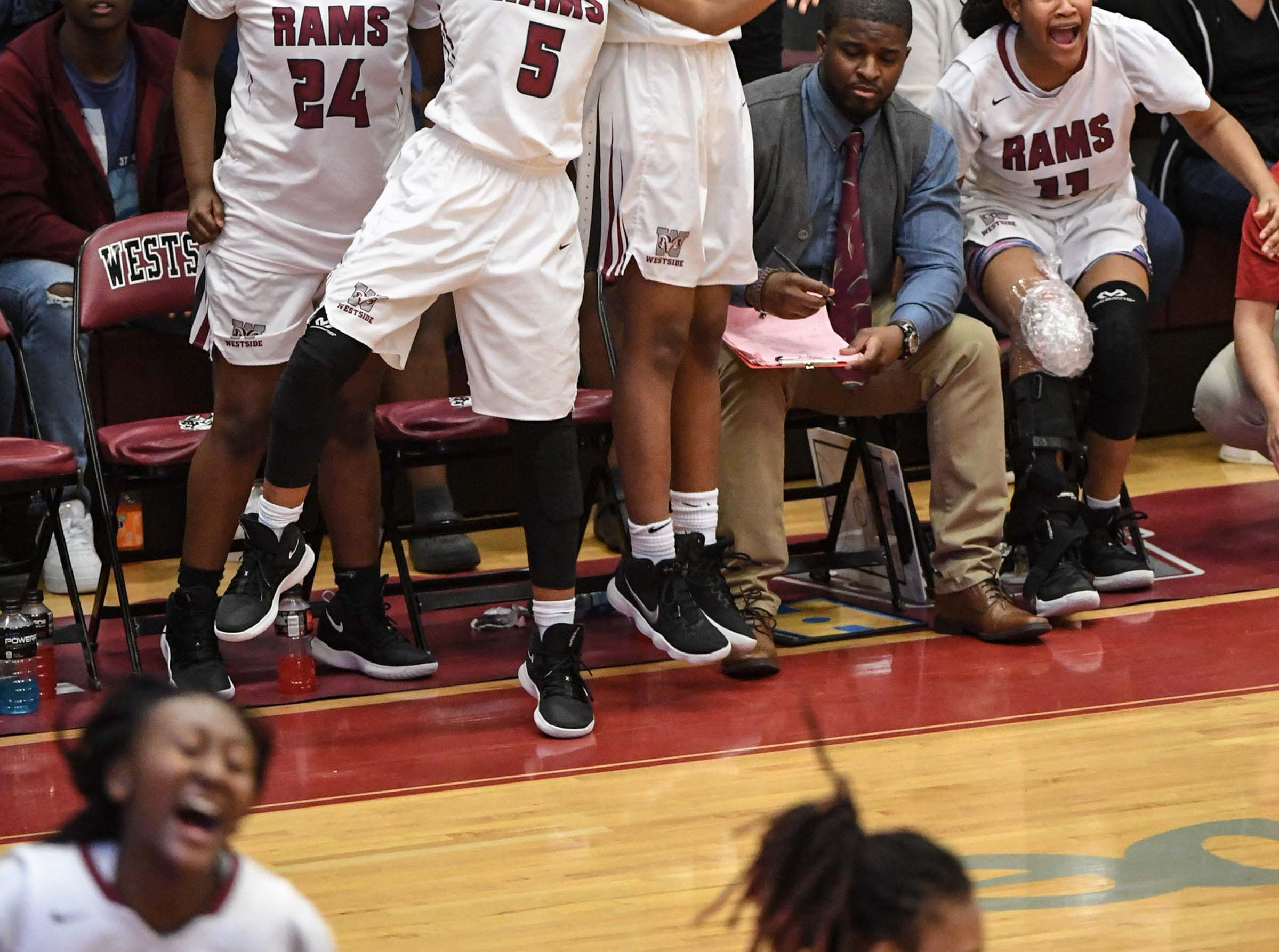 Westside senior Chelsea Adger(5) celebrates with teammates from the bench after Westside junior Tatyana Lewis(14) scored during the fourth quarter at Westside High School in Anderson on Friday. Westside won 54-46.