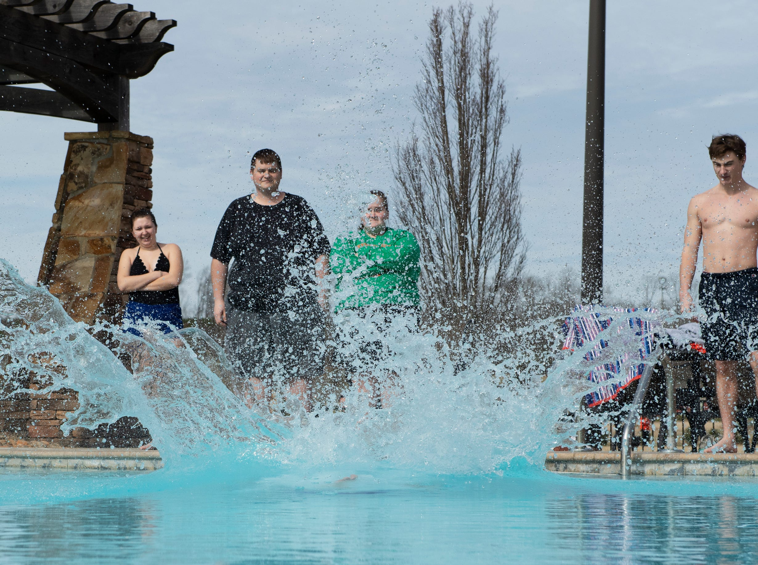 Shane Winslow jumps in to check the pool temperature before polar plungers enter the water for the 2019 Tiger Paw Polar Plunge at in the pool at The Pier housing complex in Seneca Saturday, Feb. 9, 2019. He read that the water was 58 degrees.