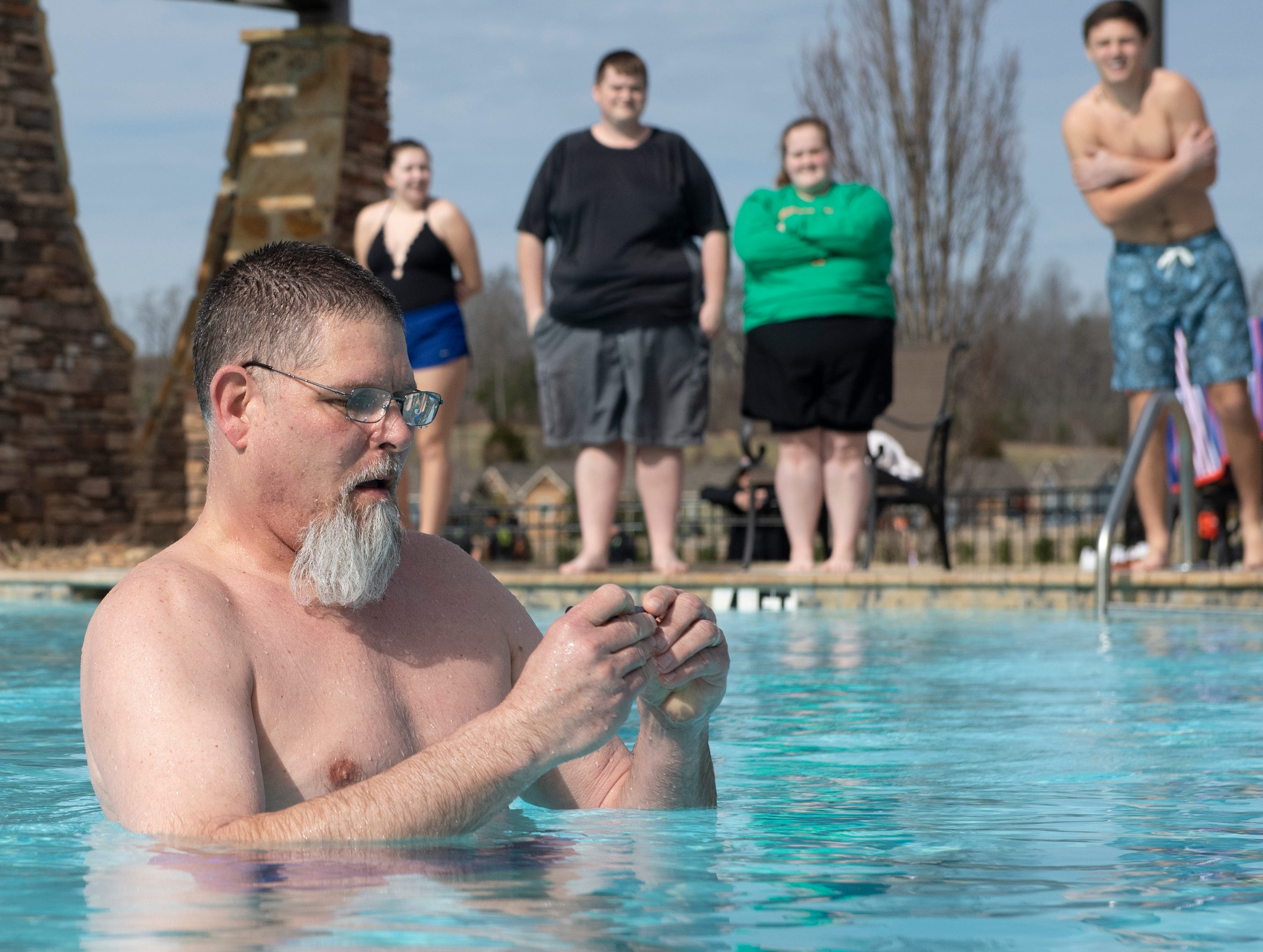 Shane Winslow checks the pool temperature before polar plungers enter the water for the 2019 Tiger Paw Polar Plunge at in the pool at The Pier housing complex in Seneca Saturday, Feb. 9, 2019. He read that the water was 58 degrees.