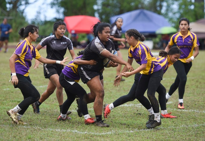 Simon Sanchez player Angelyn Sobrevilla shoves a George Washington Geckos defender during a run in their IIAAG Girls' Rugby match at the Southern High School Field, Feb. 9, 2019.