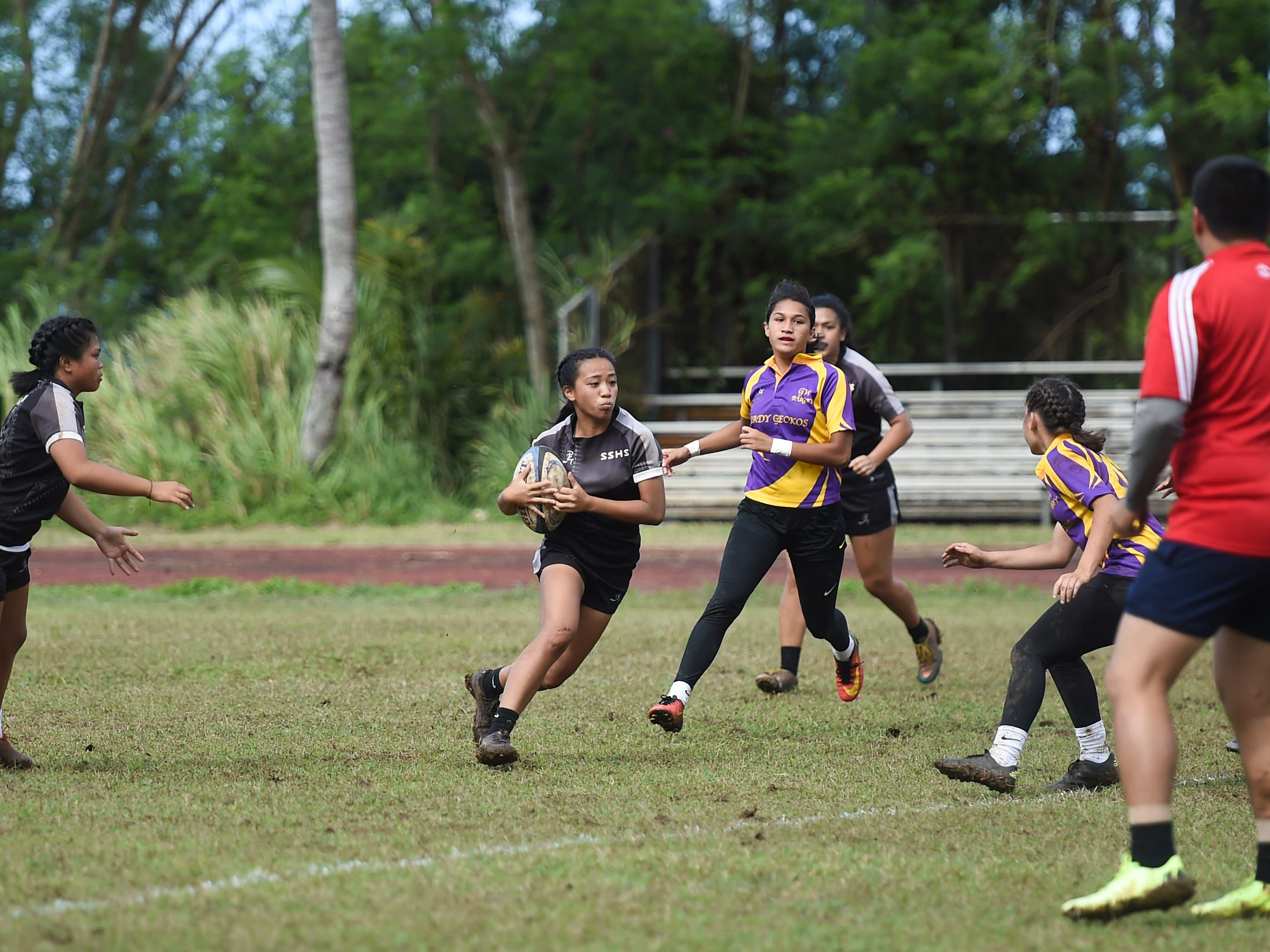 Simon Sanchez player Sherald Alvarez runs the ball against the George Washington Geckoa for their IIAAG Girls' Rugby match at the Southern High School Field, Feb. 9, 2019.