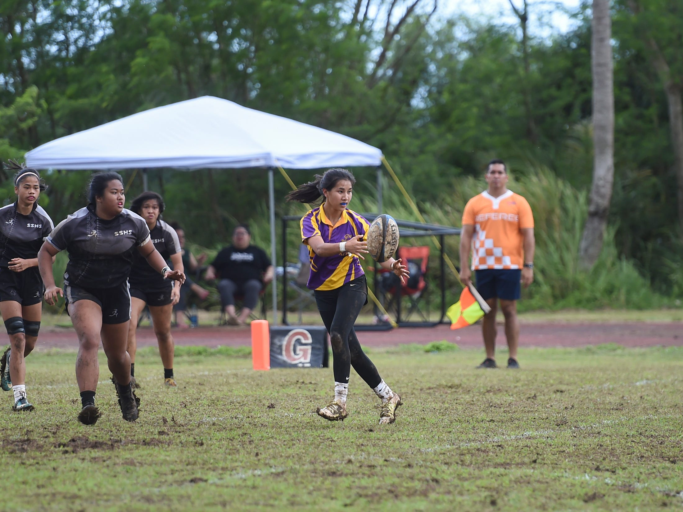 George Washington's Sawyer Park (8) makes a pass during a IIAAG Girls' Rugby match against the Simon Sanchez Sharks at the Southern High School Field, Feb. 9, 2019.