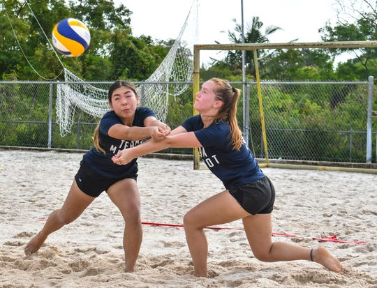 Harvest Christian Academy Eagles' Trinity Terlaje, left, and Natalie Bruch get their signals crossed after a serve from the St. John's Knights White team during an IIAAG beach volleyball game at the Guam Football Association National Training Center in Dededo on Saturday, Feb. 9, 2019.