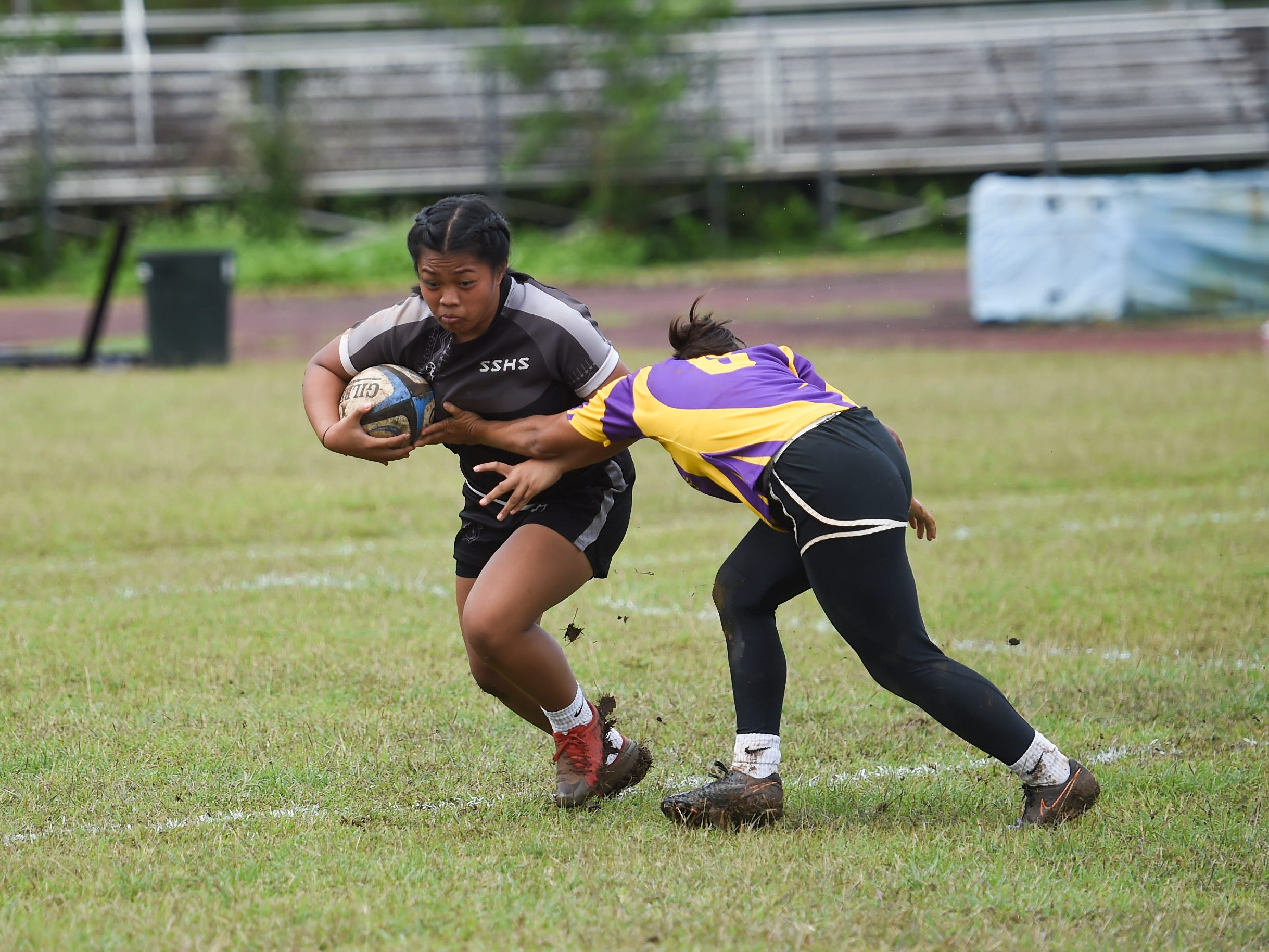 Simon Sanchez player Joanne Alvarez attempts to push through a tackle by a George Washington player during their IIAAG Girls' Rugby match at the Southern High School Field, Feb. 9, 2019.