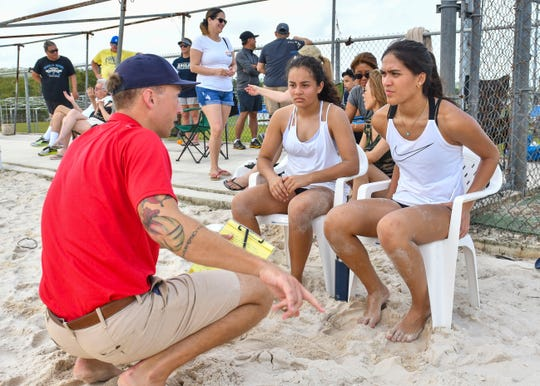 St. John's Knights White team's Laressa Halladay, right, and teammate, Hana Fernandea listen to strategic advice given by their coach, Logan Woodke, during an IIAAG beach volleyball game against Harvest Christian Academy Eagles at the Guam Football Association National Training Center in Dededo on Saturday, Feb. 9, 2019.