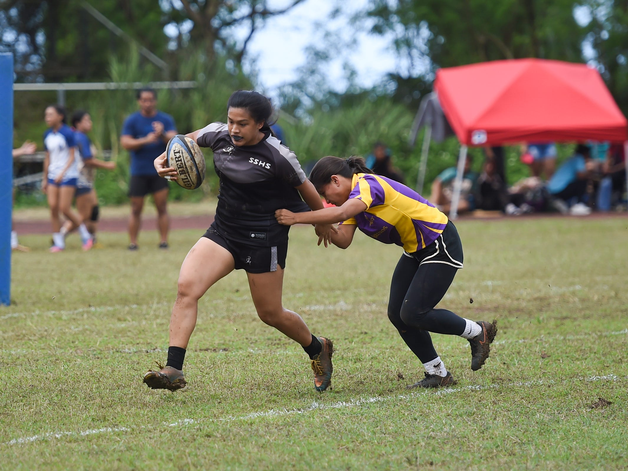 Simon Sanchez player T'anna Dela Cruz attempts to elude a Geckos defender during their IIAAG Girls' Rugby match at the Southern High School Field, Feb. 9, 2019.