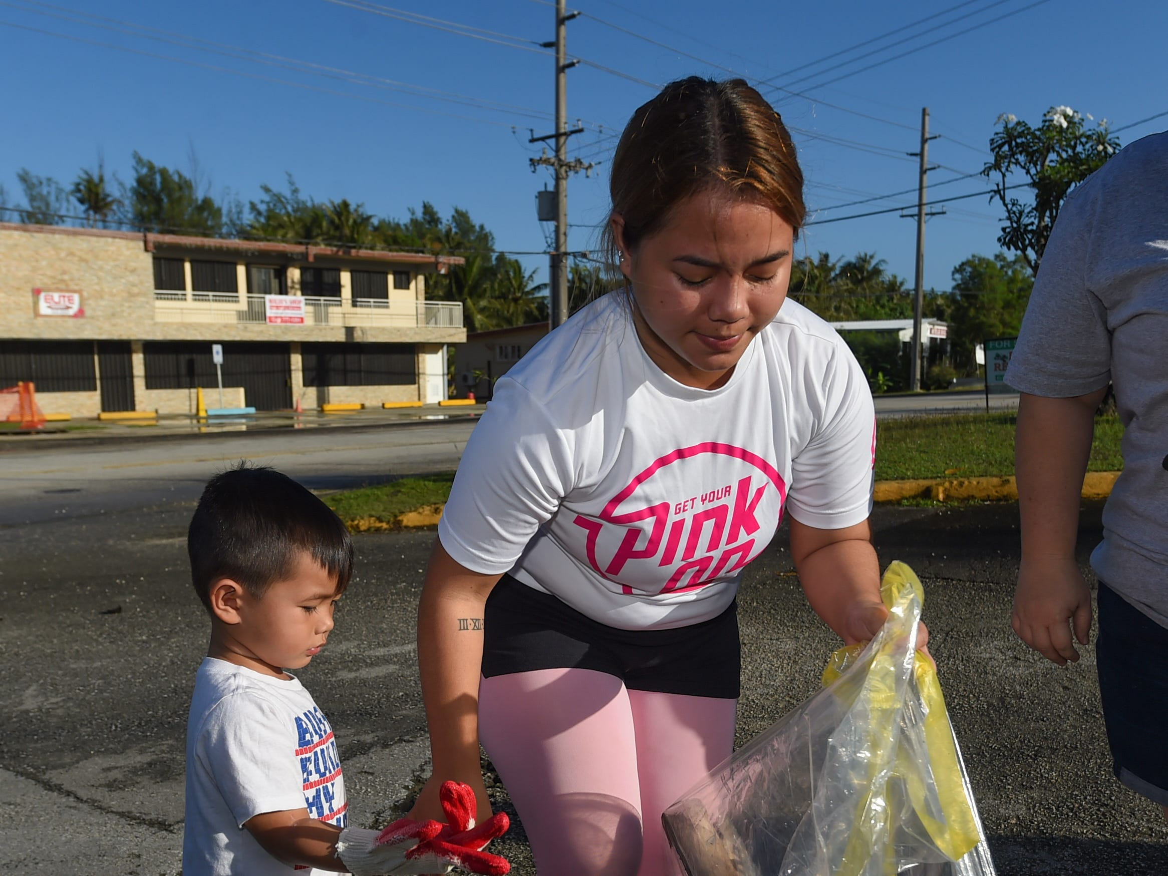 Four-year-old Connor Cundiff helps his mom, KalinaJay Cundiff, during the annual Na' Bonita Hagat village cleanup in Agat on Feb. 9, 2019.