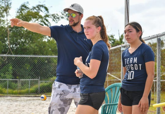 Harvest Christian Academy Eagles' Trinity Terlaje, right, and Natalie Burch listen to strategic advice given by their coach, Matt Noland, during an IIAAG beach volleyball game against St. John's Knights White team at the Guam Football Association National Training Center in Dededo on Saturday, Feb. 9, 2019.