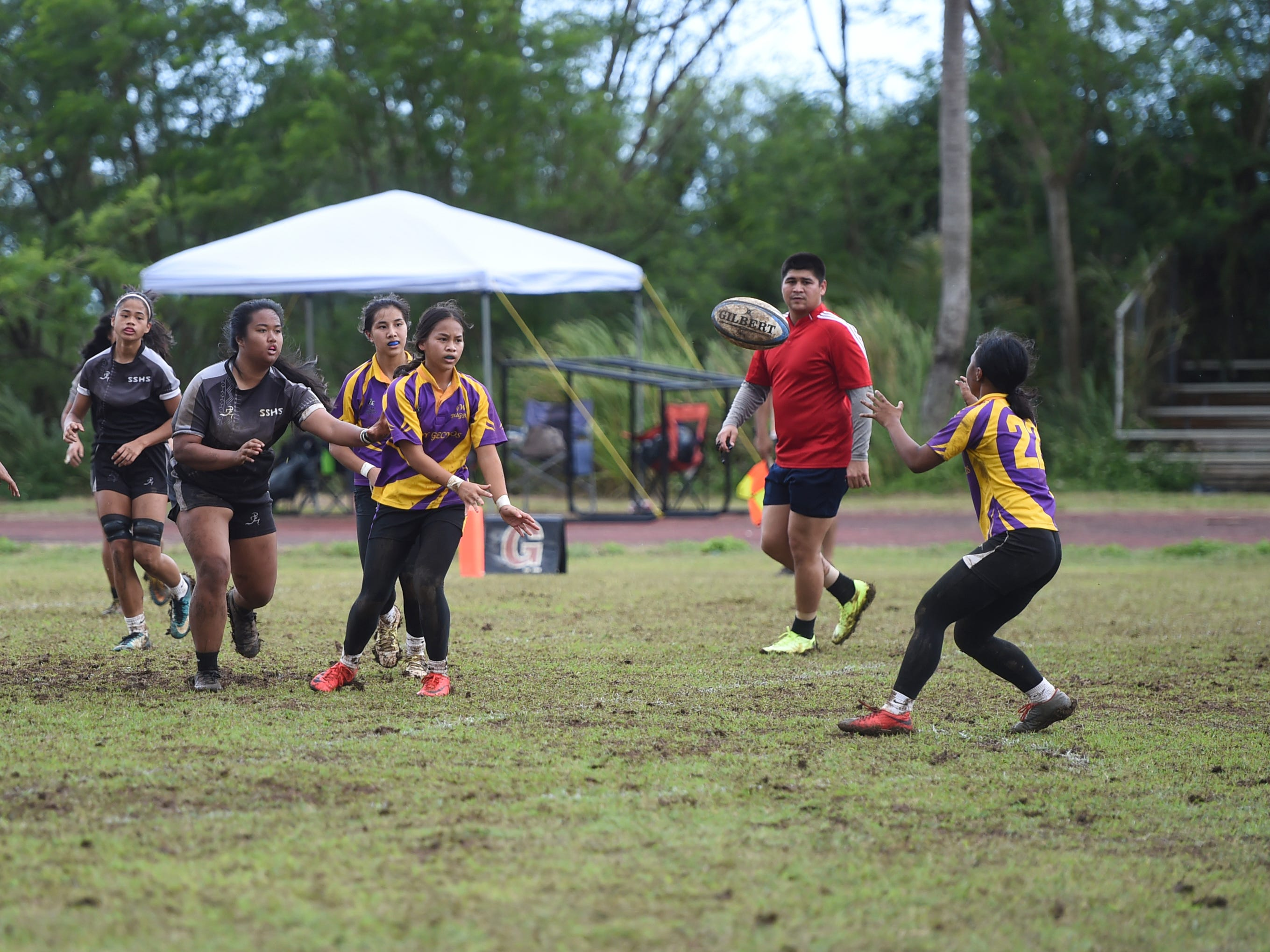 George Washington Geckos player Frankie Unchangco passes to Daeline Pangelinan (22) during their IIAAG Girls' Rugby match at the Southern High School Field, Feb. 9, 2019.
