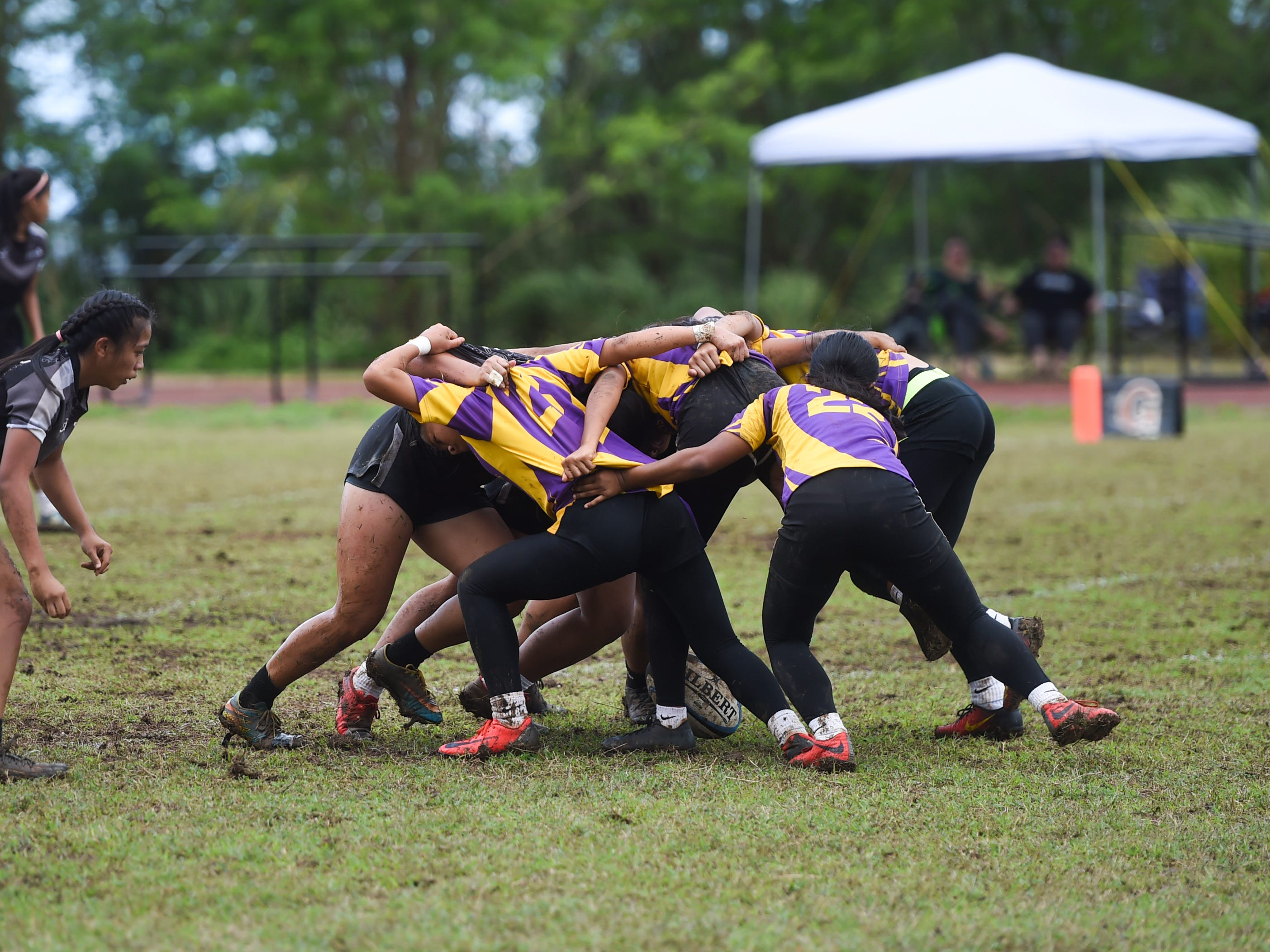 Simon Sanchez Sharks and George Washington Geckos players engage in a scrum during their IIAAG Girls' Rugby match at the Southern High School field, Feb. 9, 2019.