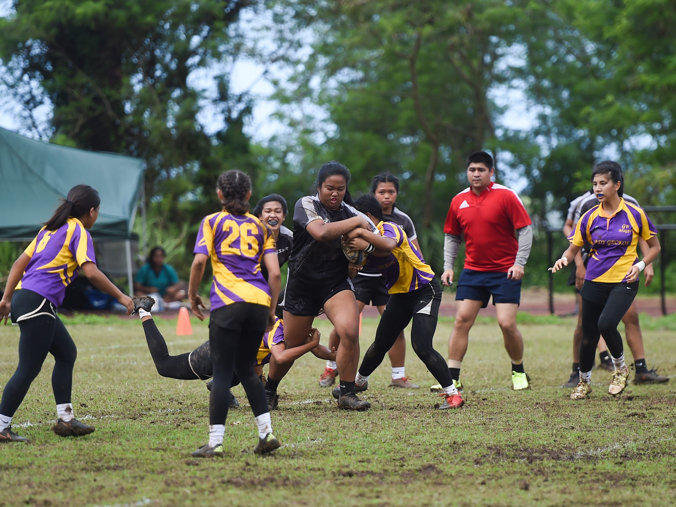 Simon Sanchez player Angelyn Sobrevilla charges through George Washington Geckos defenders in their IIAAG Girls' Rugby match at the Southern High School Field, Feb. 9, 2019.