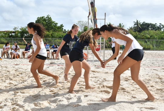 Harvest Christian Academy Eagles and St. John's Knights White team exchange gestures of sportsmanship as they switch courts during an IIAAG beach volleyball game at the Guam Football Association National Training Center in Dededo on Saturday, Feb. 9, 2019.