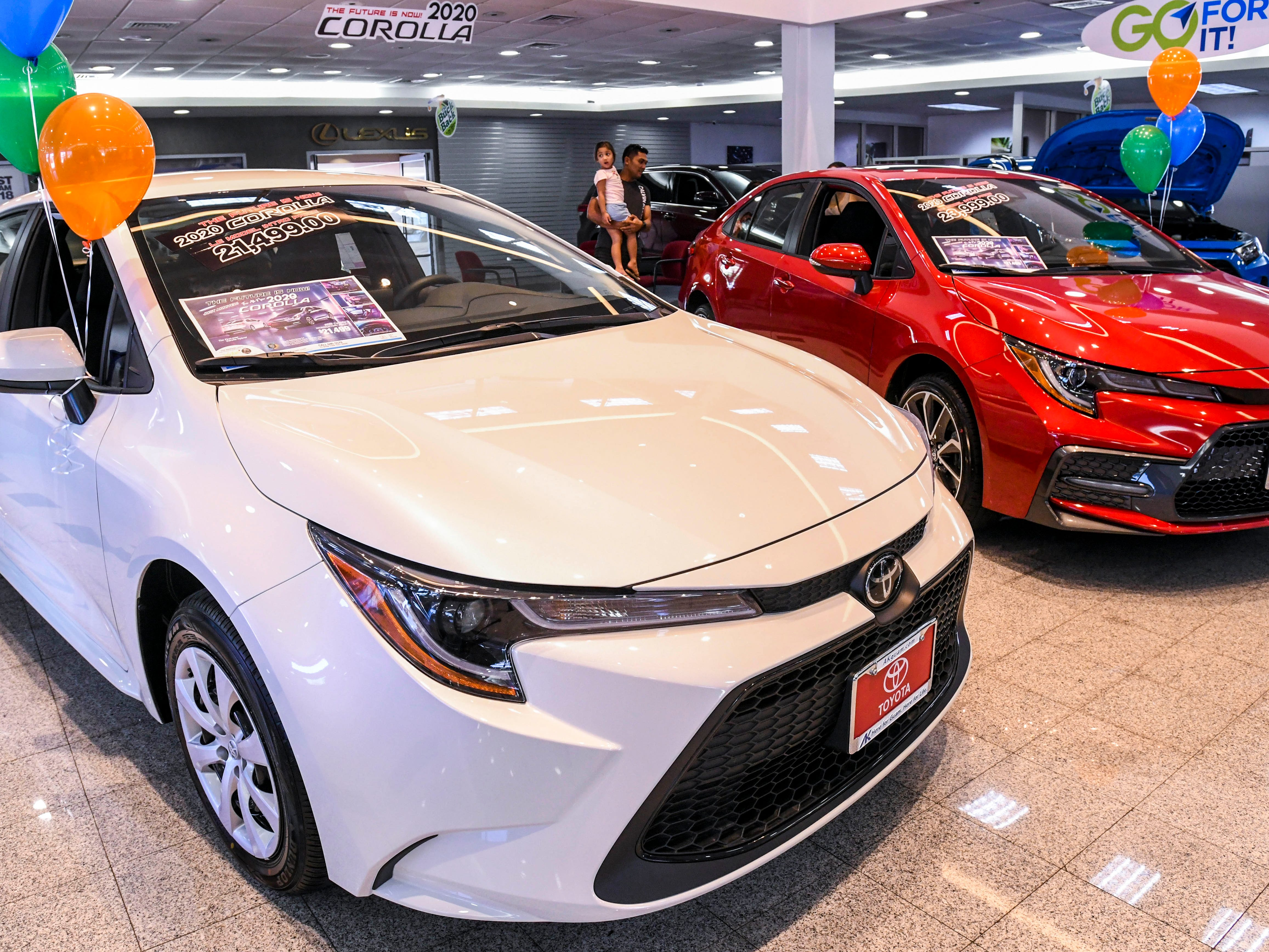 Prospective car shoppers look over the two models of the newly redesigned 2020 Toyota Corolla, as seen on the showroom floor of the Atkins Kroll dealership in Tamuning, on Saturday, Feb. 9, 2019. Atkins Kroll has rolled out three models of the sedan: Toyota Corolla LE (Luxury Edition), front; the Toyota Corolla SE (Sport Edition), right, and a Toyota Corolla HE (Hybrid Edition), not seen.