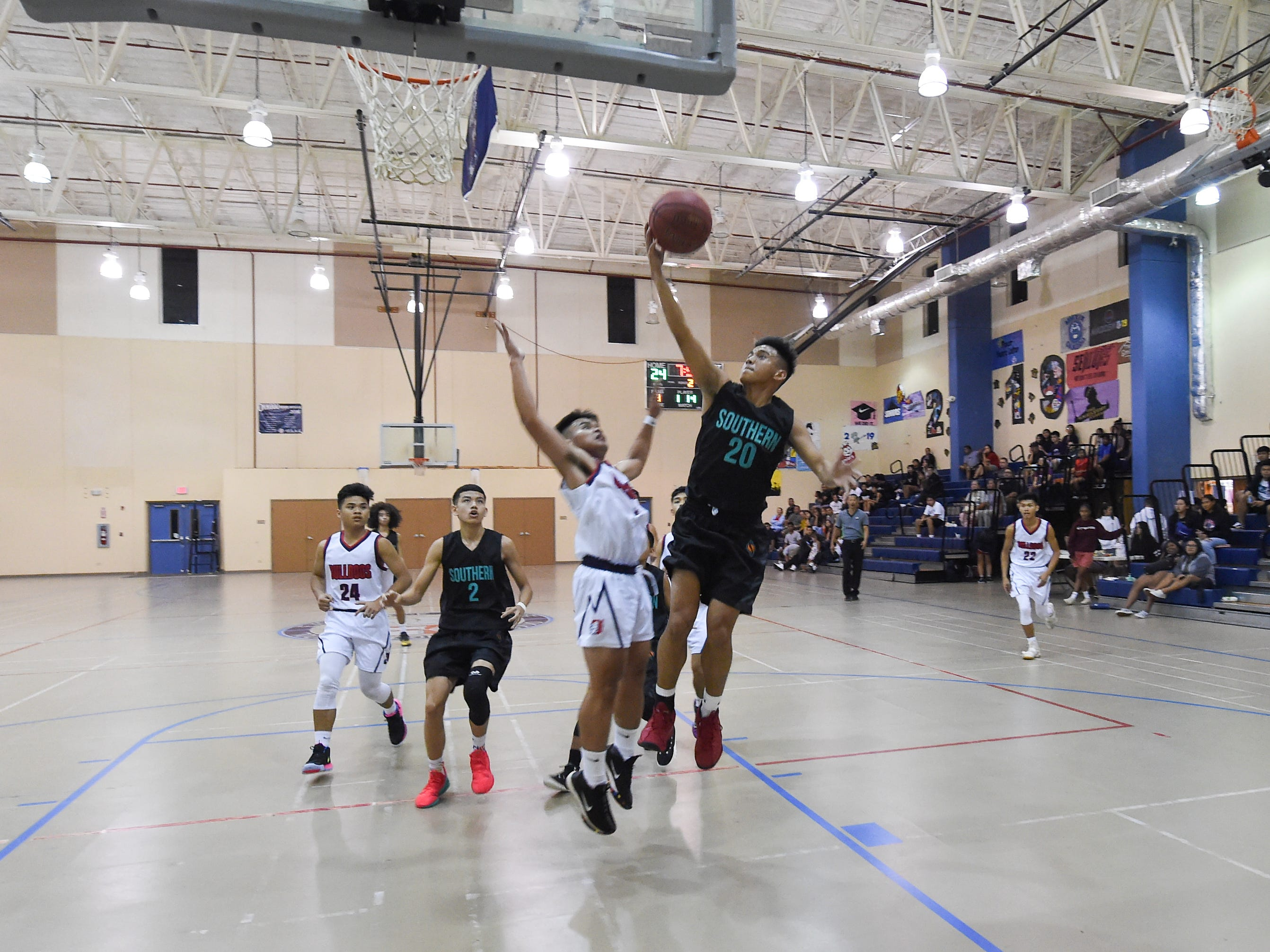 Southern Dolphins player Shawn Santiago (20) drives baseline against the Okkodo Bulldogs during their IIAAG Boys' Basketball game at the Okkodo High School Gym, Feb. 8, 2019.