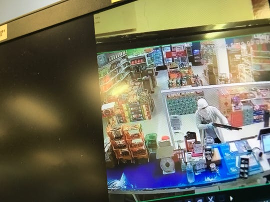 This screenshot from security camera footage shows masked suspect points a rifle across the counter at Loco Mart in Dededo on Friday, Feb. 8, 2019.