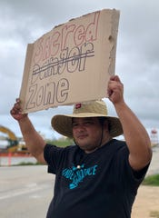 Jesse Chargualaf holds up a sign peacefully protesting against the proposed surface danger zone at Finegayan.