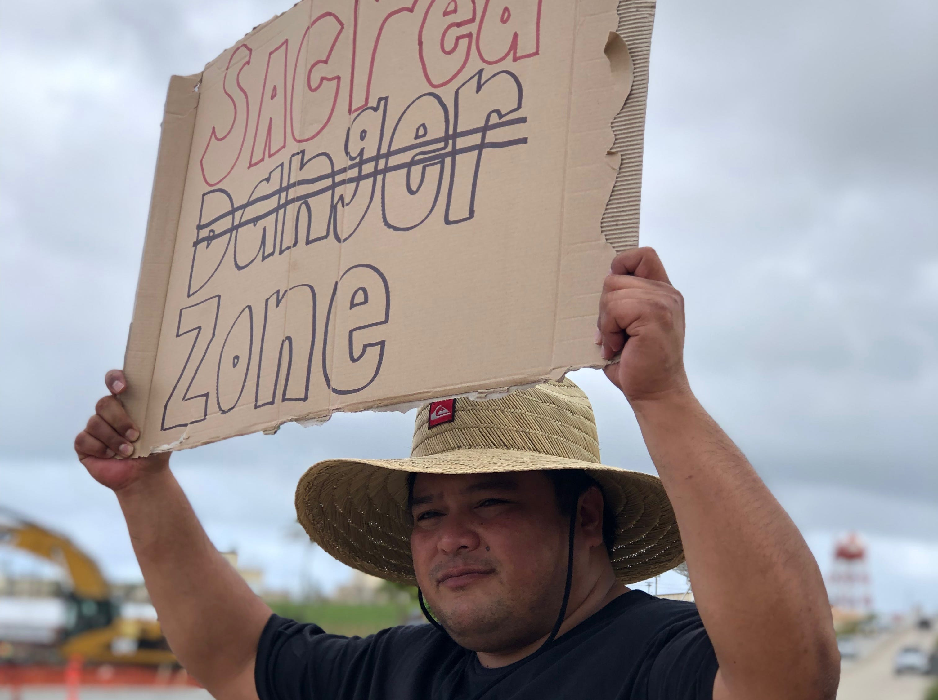 Jesse Chargualaf holds up a sign peacefully protesting against the proposed surface danger zone at Finegayan. Groups of people protested along Route 3 and in boats near the proposed zone on Saturday, Feb. 9, 2019.