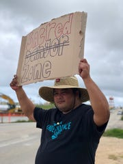 In this Feb. 9 file photo, Jesse Chargualaf holds up a sign peacefully protesting against the proposed surface danger zone at Finegayan.