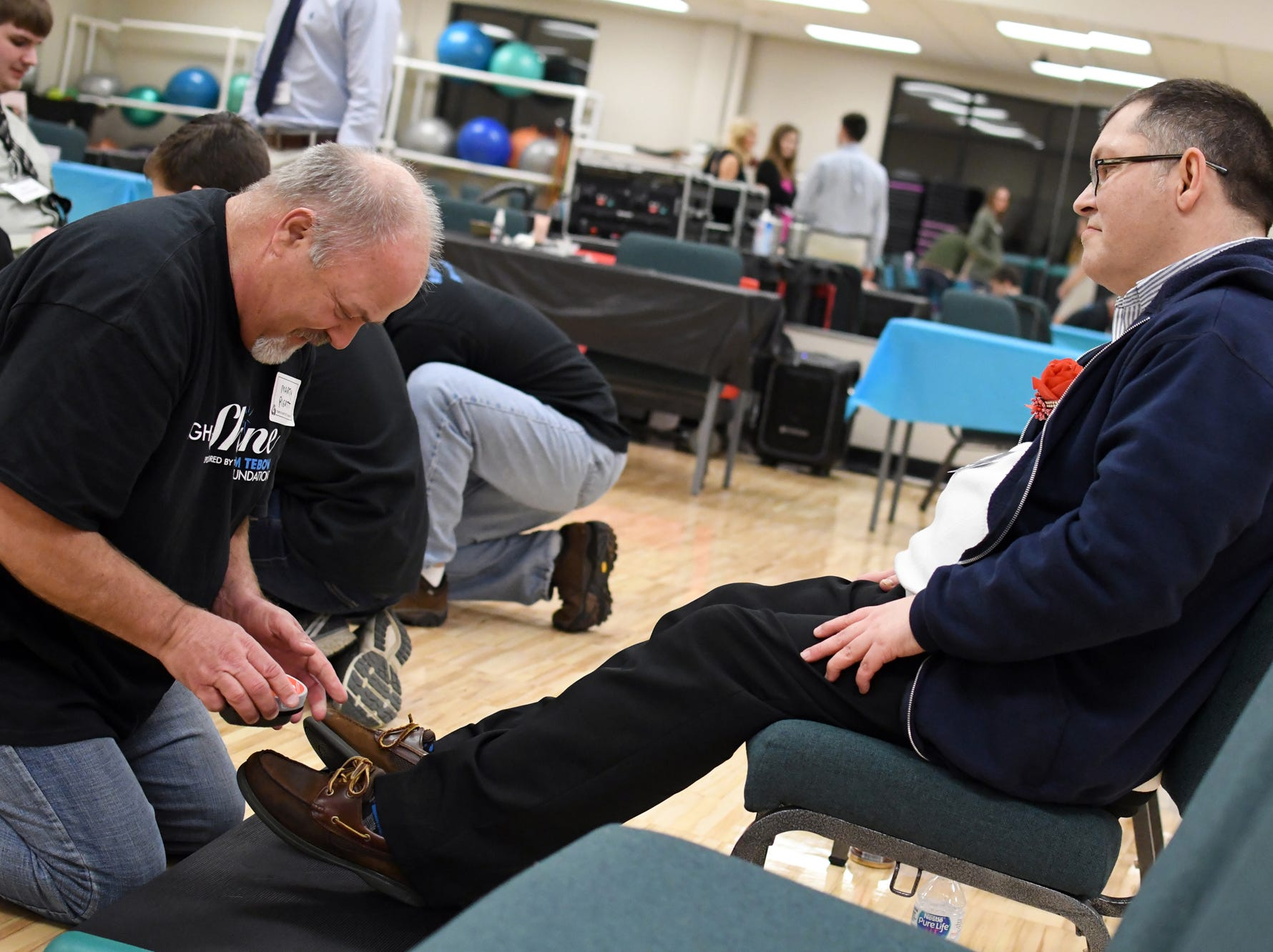 Prom guests gets his shoes polished during the Night to Shine Prom at Temple Baptist Church on Friday, February 8, 2019. Churches around the world hosted the prom by the Tim Tebow Foundation for people with special needs.