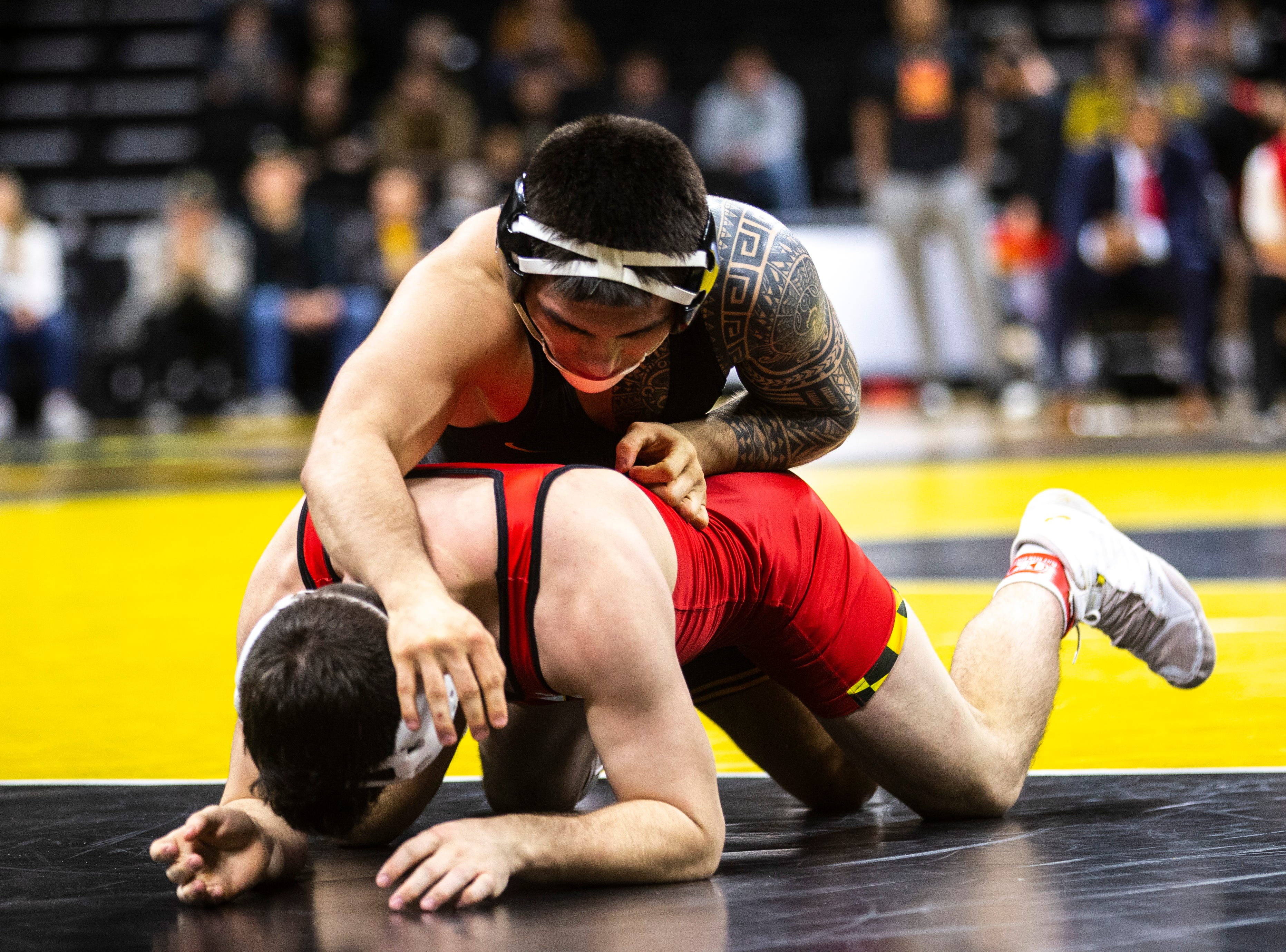 Iowa's Pat Lugo, top, wrestles Maryland's Pete Tedesco at 149 during a NCAA Big Ten Conference wrestling dual on Friday, Feb. 8, 2019 at Carver-Hawkeye Arena in Iowa City, Iowa.