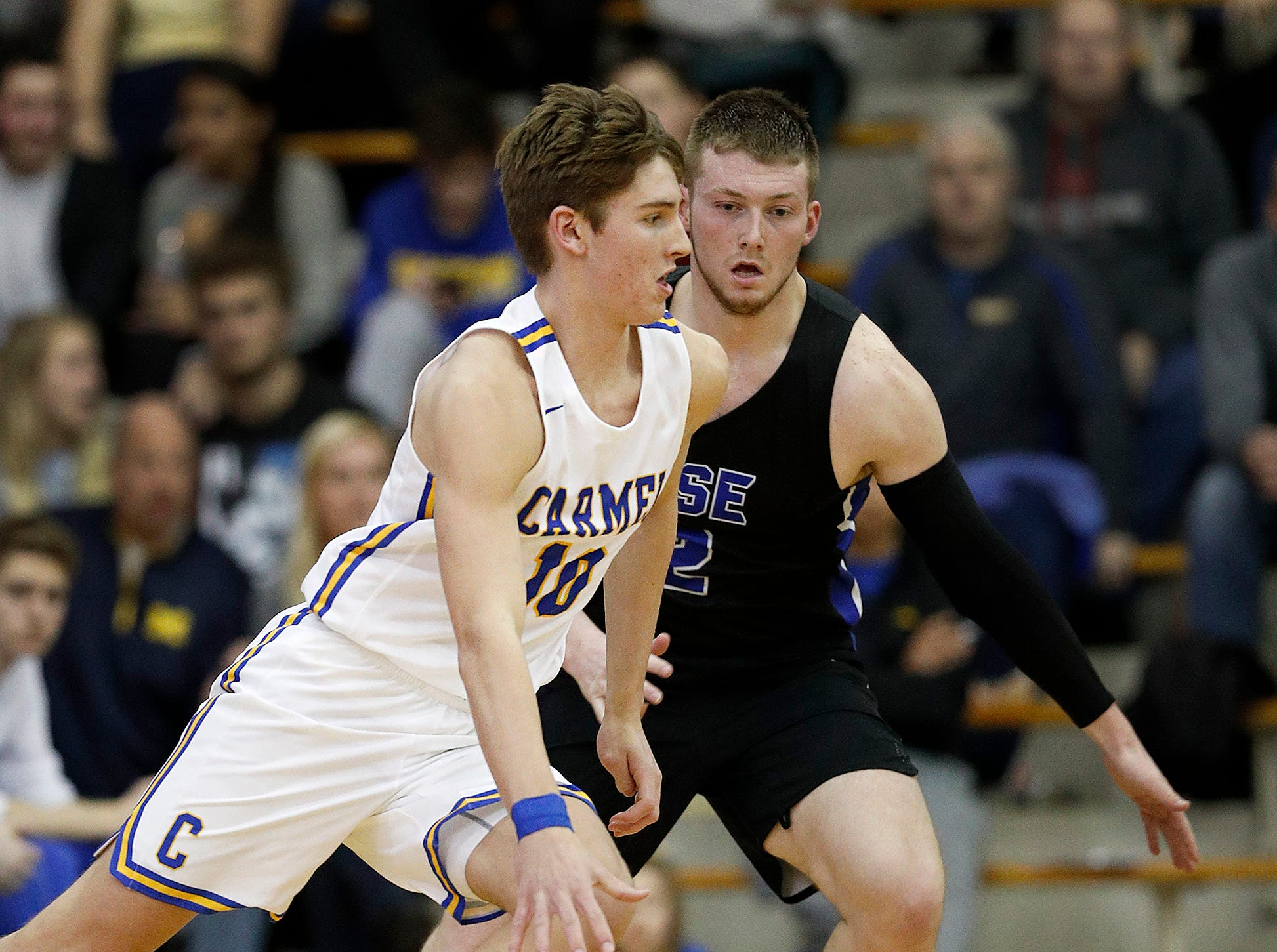Carmel Greyhounds Peter Suder (10) drives on Hamilton Southeastern Royals Aaron Etherington (2) in the second half of their game at Carmel High School on Friday, Feb. 8, 2019.