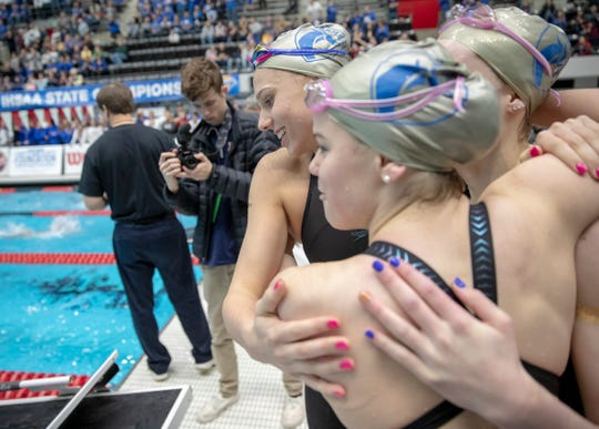 Carmel High School swimmers huddle up after their win in the 400 yard freestyle relay, IHSAA Girls State Swimming and Diving Finals, IUPUI Natatorium, Indianapolis, Saturday, Feb. 9, 2019. Carmel High School has won 33 straight state titles, extending their national record.