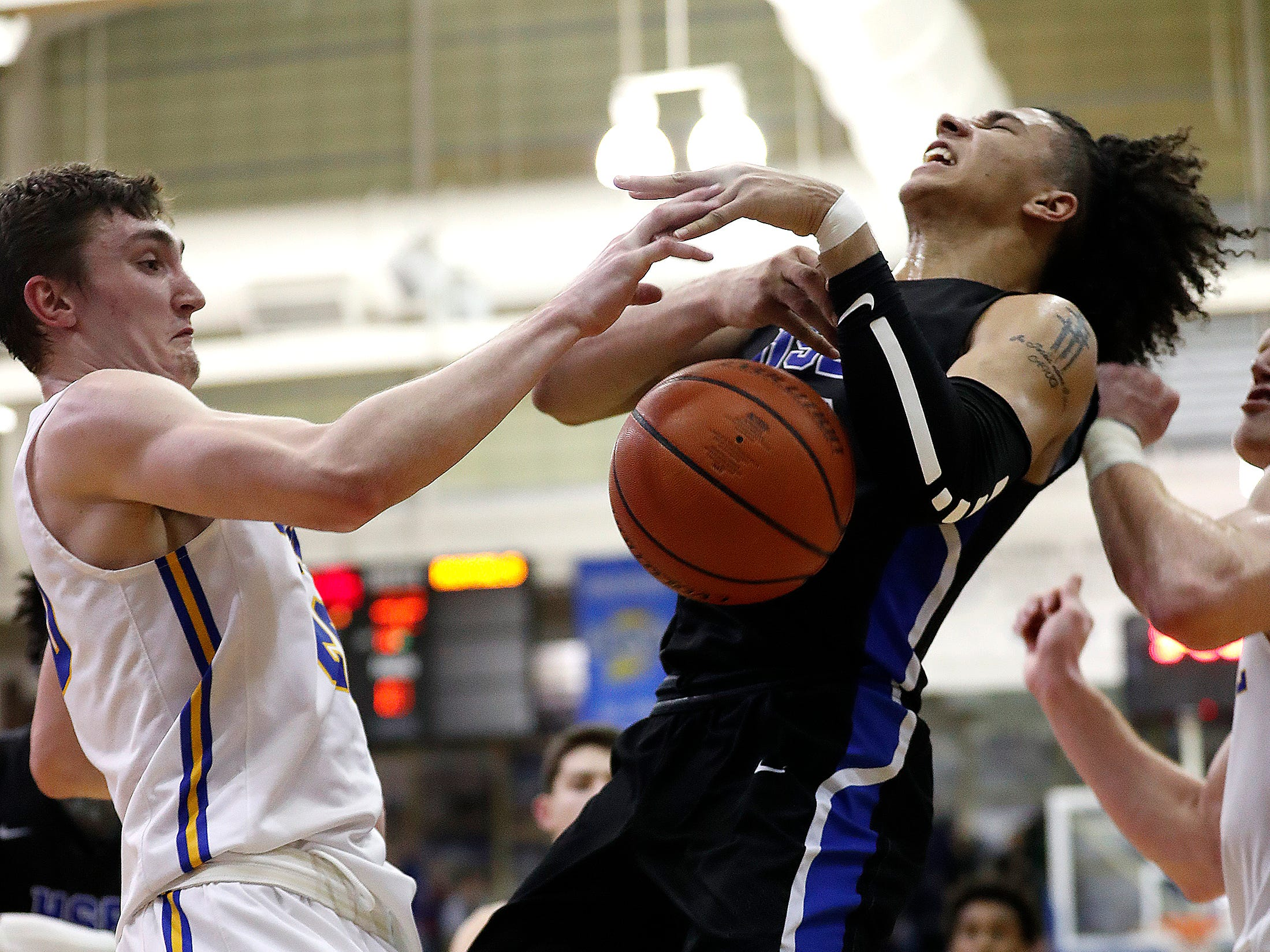 Hamilton Southeastern Royals Chris Grubbs (20) is fouled by Carmel Greyhounds Andrew Owens (20) in the second half of their game at Carmel High School on Friday, Feb. 8, 2019.