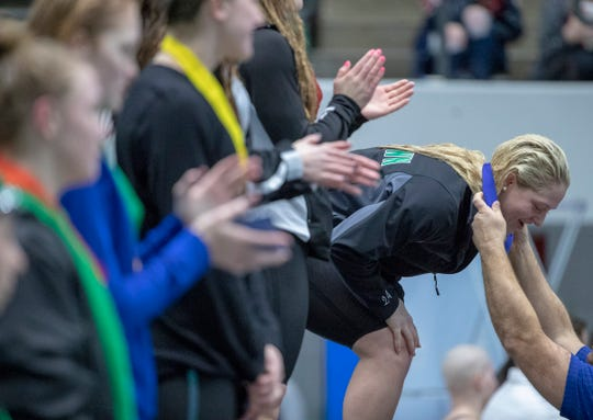 Emily Weiss of Yorktown High School, one of the strongest swimmers in the country, accepts her medal after her victory in the 100 yard breaststroke, during the IHSAA Girls State Swimming and Diving Finals, IUPUI Natatorium, Indianapolis, Saturday, Feb. 9, 2019. Carmel High School, the team winner, has won 33 straight state titles, extending their national record.