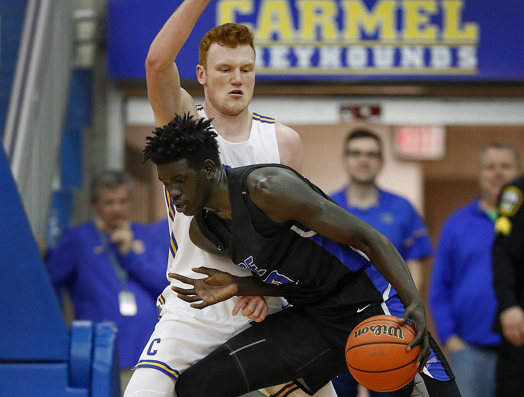 Hamilton Southeastern Royals Mabor Majak (50) drives to the basket on Carmel Greyhounds John Michael Mulloy (33) in the first half of their game at Carmel High School on Friday, Feb. 8, 2019.