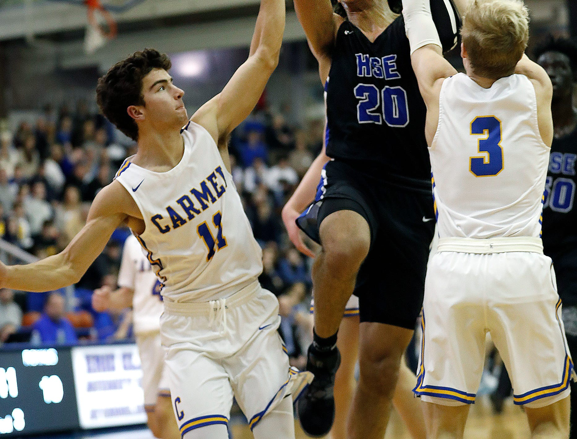 Carmel Greyhounds Luke Heady (11) and Karsten Windlan (3) attempt to stop Hamilton Southeastern Royals Chris Grubbs (20) in the second half of their game at Carmel High School on Friday, Feb. 8, 2019.