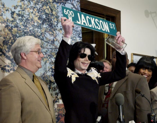 Michael Jackson holds up a street sign and key to the city given him by Gary Mayor Scott King at a press conference at City Hall on Wednesday June 11, 2003. Jackson returned to his hometown of Gary for the first time since his childhood.