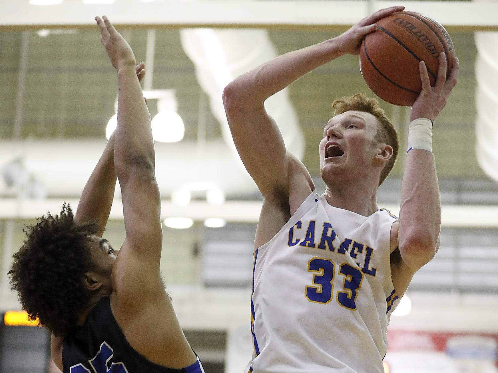 Carmel Greyhounds John Michael Mulloy (33) shoots over Hamilton Southeastern Royals Landon Morris (35) in the first half of their game at Carmel High School on Friday, Feb. 8, 2019.