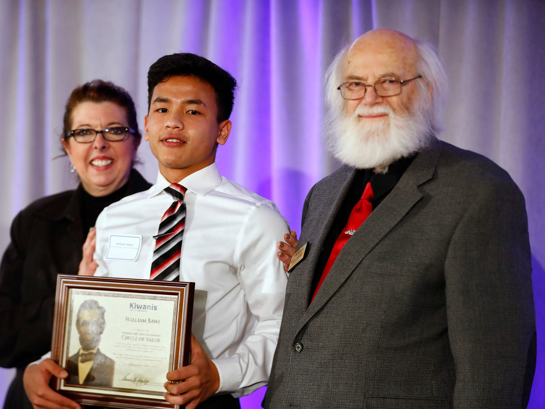 Roncalli High School student William Bawi, center, is honored with a Circle of Valor award at the 44th Annual Abe Lincoln Awards Program, Friday, Feb. 8, 2019. The Kiwanis Club of Indianapolis program was held at Ivy Tech Community College.  20 high school student were honored at the annual event which celebrates overcoming adversity in life to succeed.