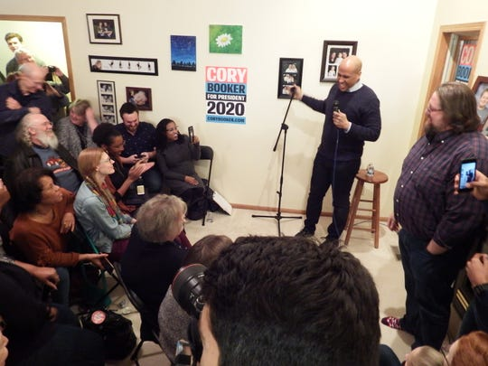 Democratic presidential candidate Senator Cory Booker (D-NJ) laughs as he hears cheers during a campaign stop at an Iowa City home on Feb. 8, 2019.