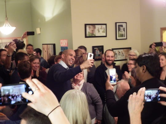 Democratic presidential candidate Senator Cory Booker (D-NJ) poses for a selfie at a campaign stop at an Iowa City home on Feb. 8, 2019.