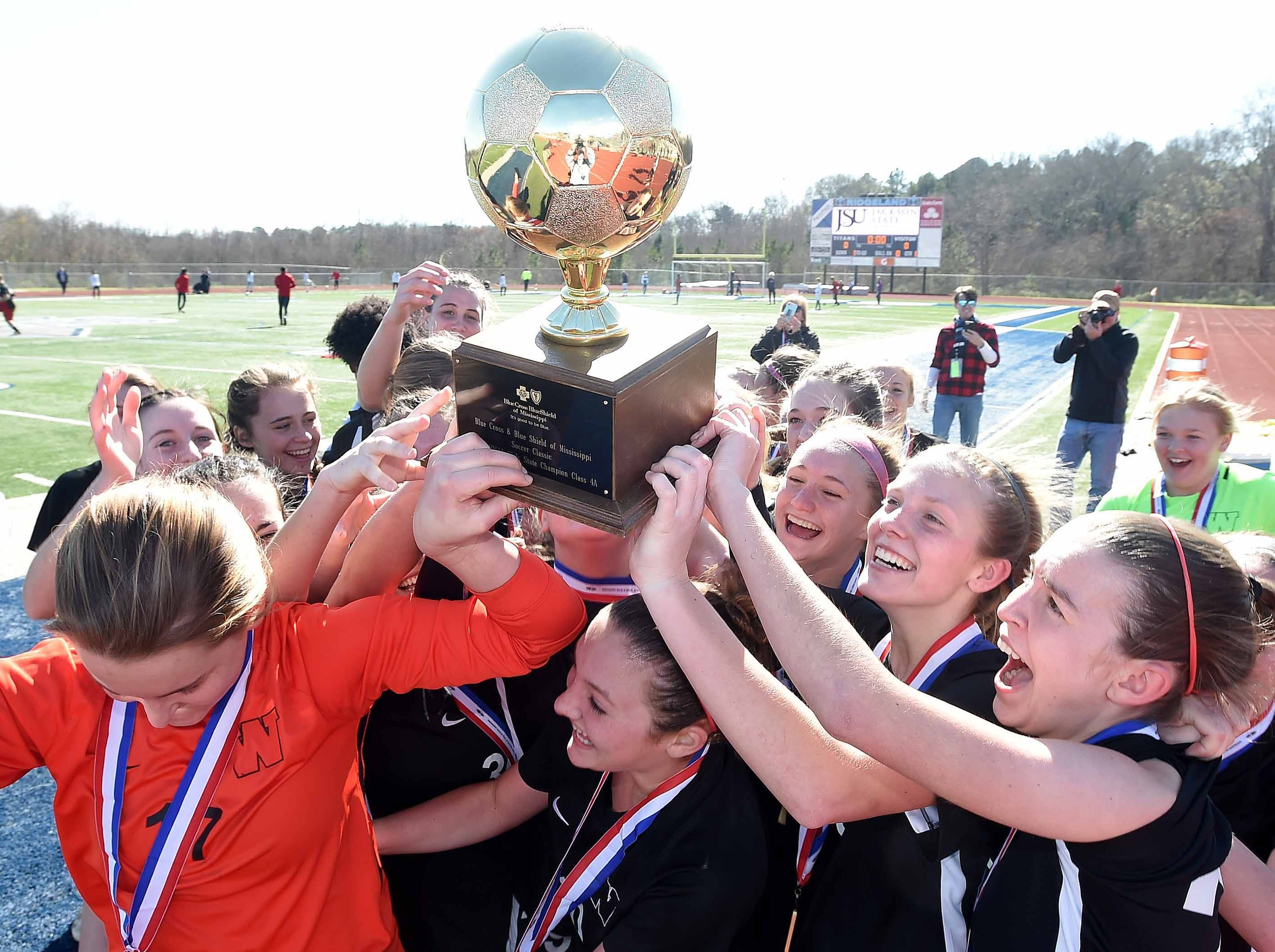 The West Lauderdale Lady Knights celebrate with the Class 4A state championship trophy after beating Florence 3-0 in the MHSAA BlueCross Blue Shield of Mississippi Soccer Classic on Saturday, February 9, 2019, at Ridgeland High School in Ridgeland, Miss.