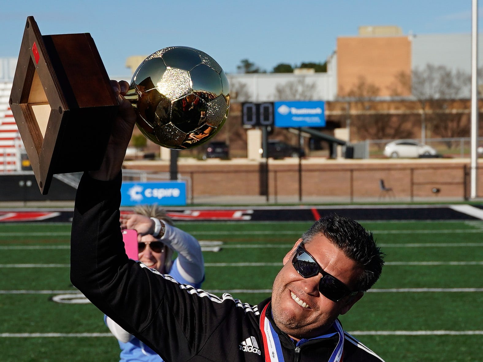 Sacred Heart boys soccer head coach Joe Falla Jr. hefts the Class 1A-2A-3A state championship trophy.