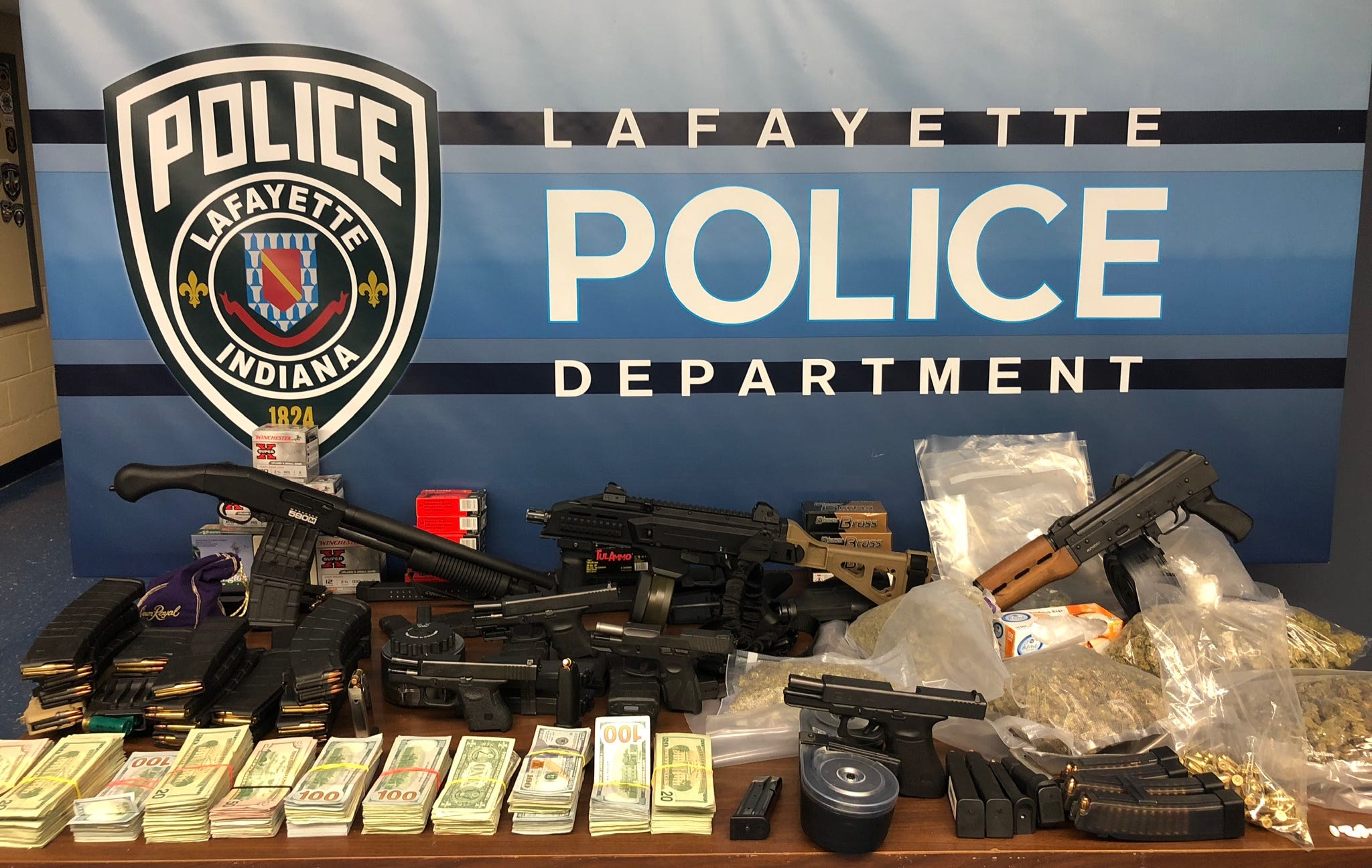 Police checking on the well being of children found more than $68,000, four pounds of marijuana and seven firearms with a cache of ammunition.