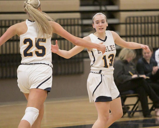 Whitney Sollom, left, congratulates fellow Hartland Eagle Madi Moyer on Moyer's three-pointer early in the first period of the home game against Brighton.