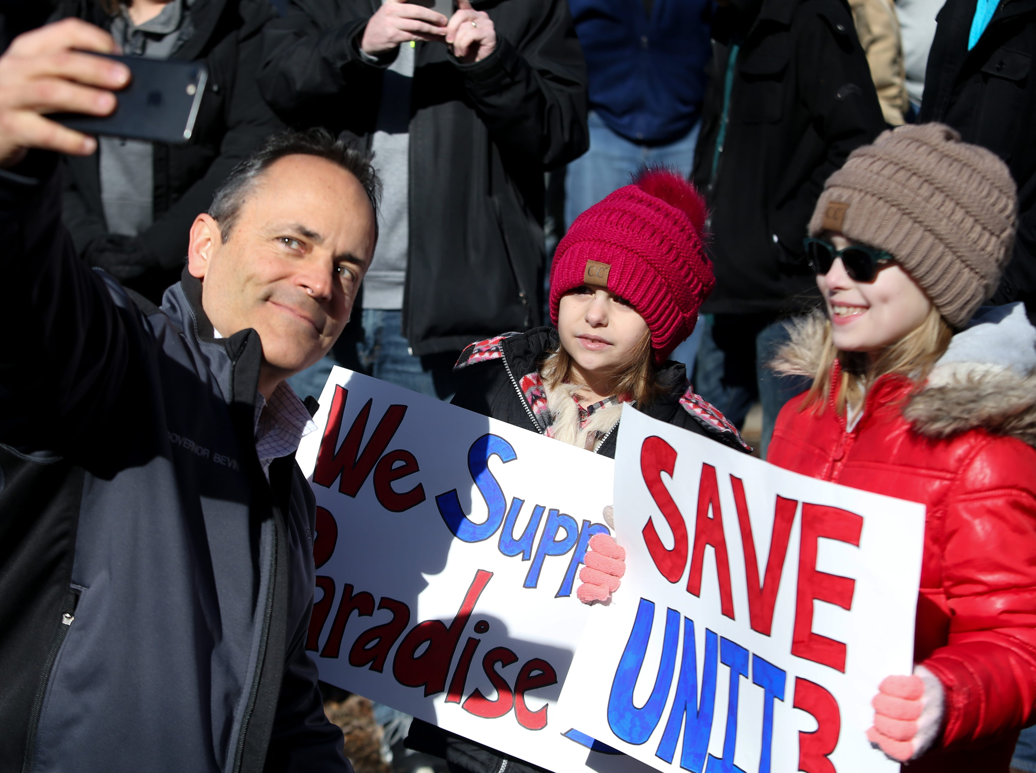 Governor Matt Bevin takes a selfie with Breanna Coin, right, and Brillee-ann Wilkerson at the rally to save the Paradise Fossil Plant in Muhlenberg County. Feb. 9, 2019