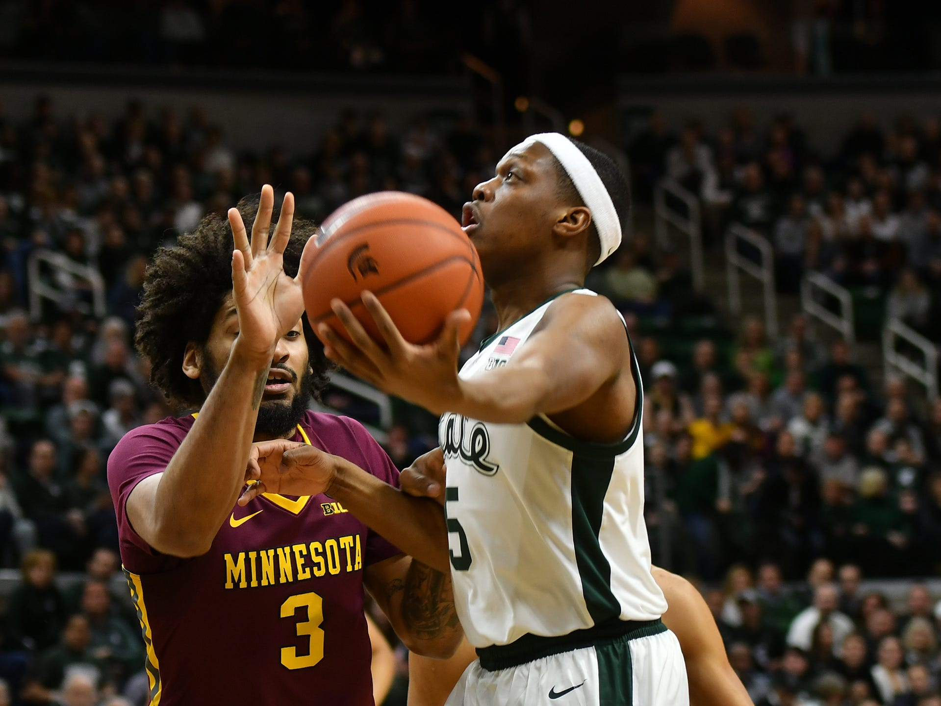 MSU's Cassius Winston (5) drives to the basket as Minnesota's Jordan Murphy (3) defends Saturday, Feb. 9, 2019.