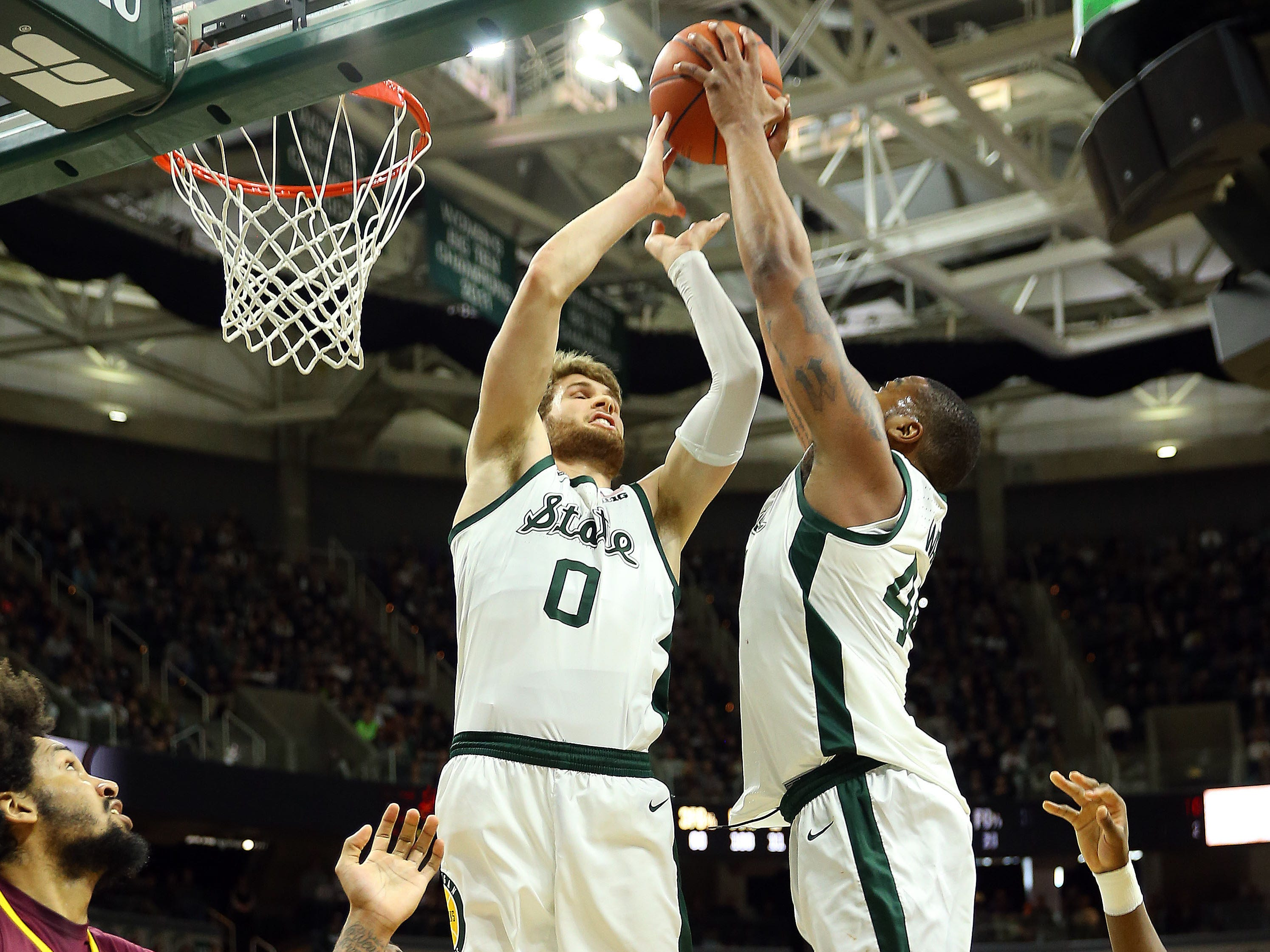 Feb 9, 2019; East Lansing, MI, USA; Michigan State Spartans forward Kyle Ahrens (0) and forward Nick Ward (44) fight for a rebound during the first half against the Minnesota Golden Gophers at the Breslin Center. Mandatory Credit: Mike Carter-USA TODAY Sports