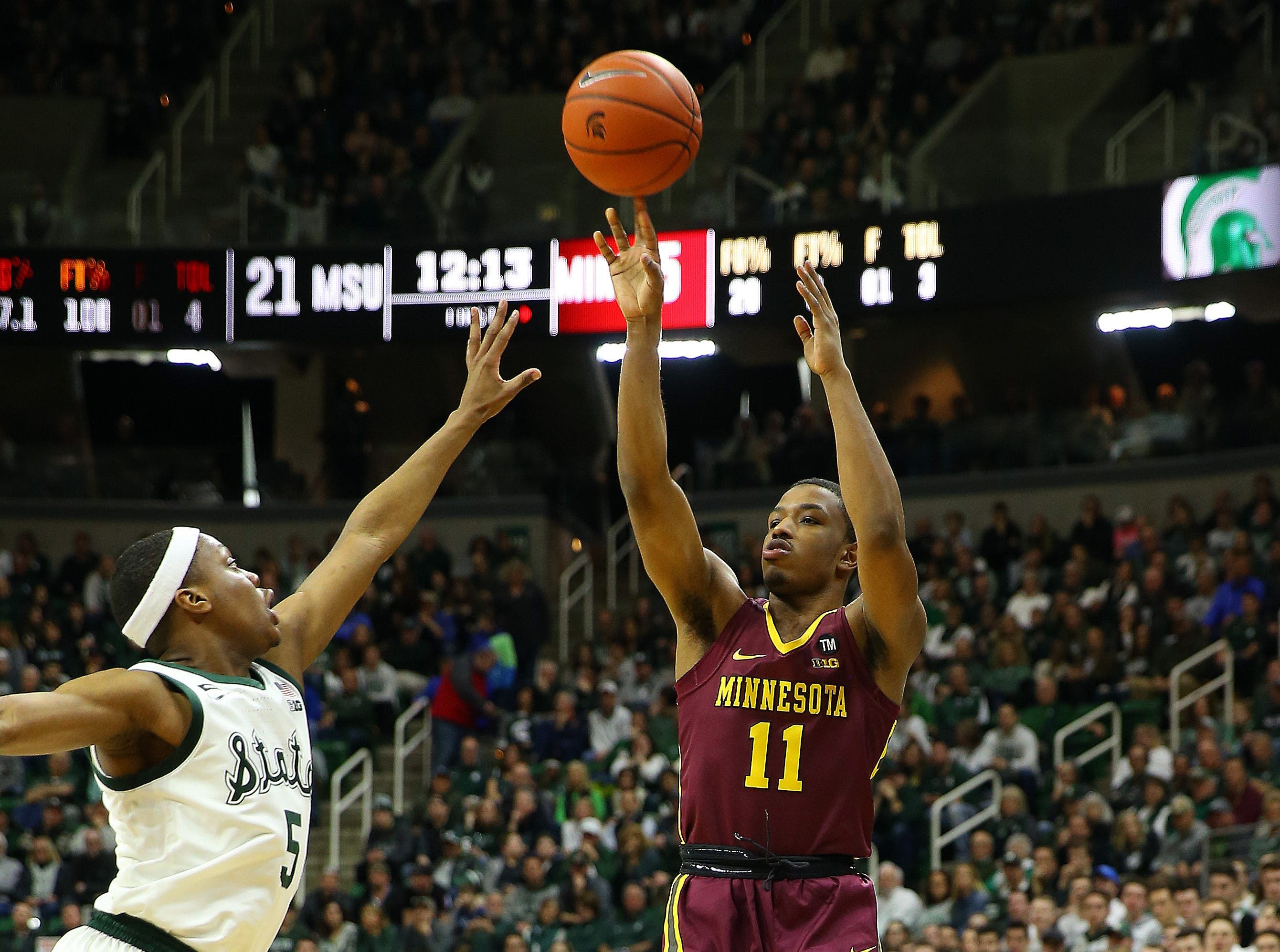 Feb 9, 2019; East Lansing, MI, USA; Minnesota Golden Gophers guard Isaiah Washington (11) shoots over Michigan State Spartans guard Cassius Winston (5) during the first half at the Breslin Center. Mandatory Credit: Mike Carter-USA TODAY Sports