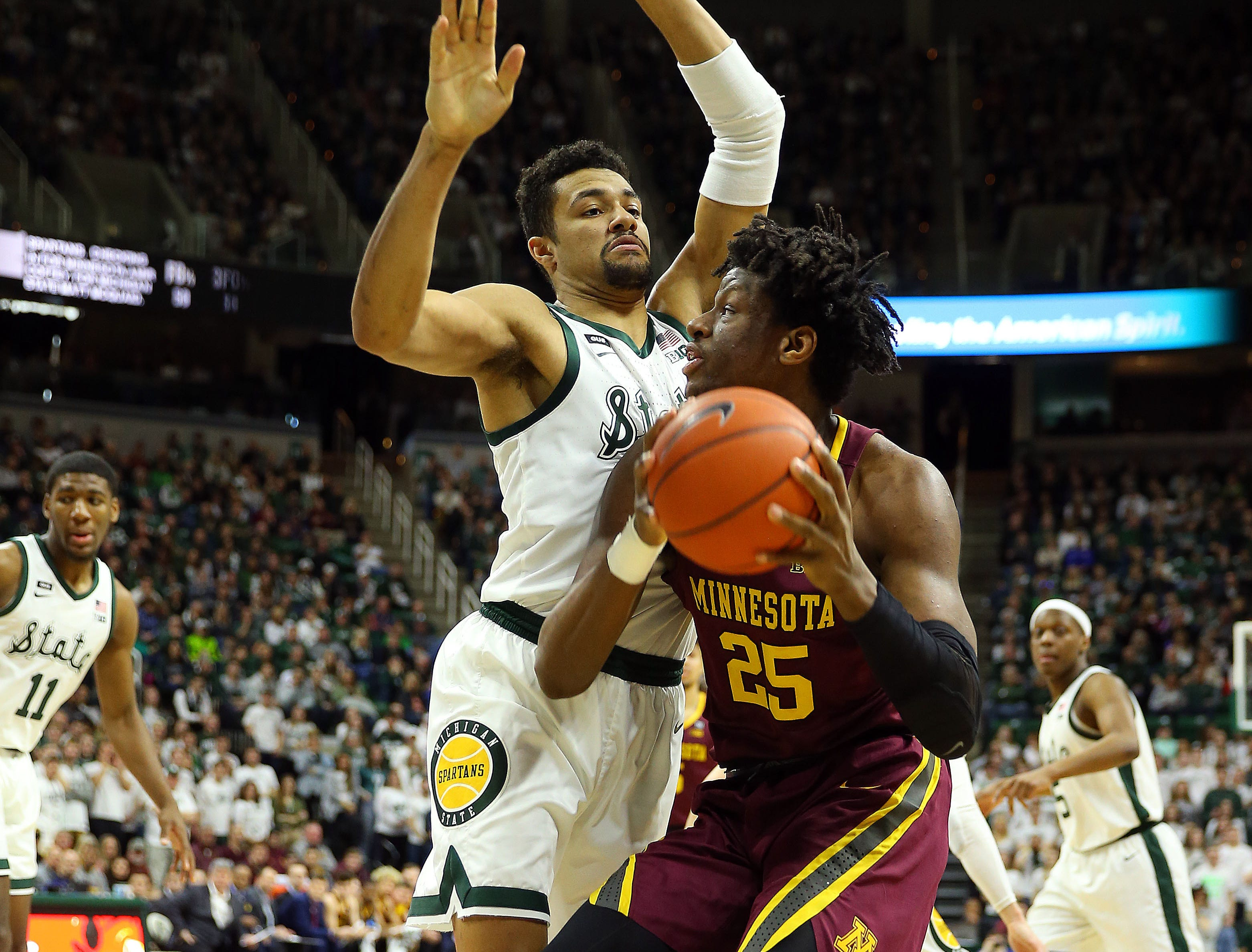 Feb 9, 2019; East Lansing, MI, USA; Minnesota Golden Gophers center Daniel Oturu (25) controls the ball against Michigan State Spartans forward Kenny Goins (25) during the first half at the Breslin Center. Mandatory Credit: Mike Carter-USA TODAY Sports