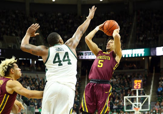 Feb 9, 2019; East Lansing, MI, USA; Minnesota Golden Gophers guard Amir Coffey (5) shoots over Michigan State Spartans forward Nick Ward (44) during the first half at the Breslin Center. Mandatory Credit: Mike Carter-USA TODAY Sports