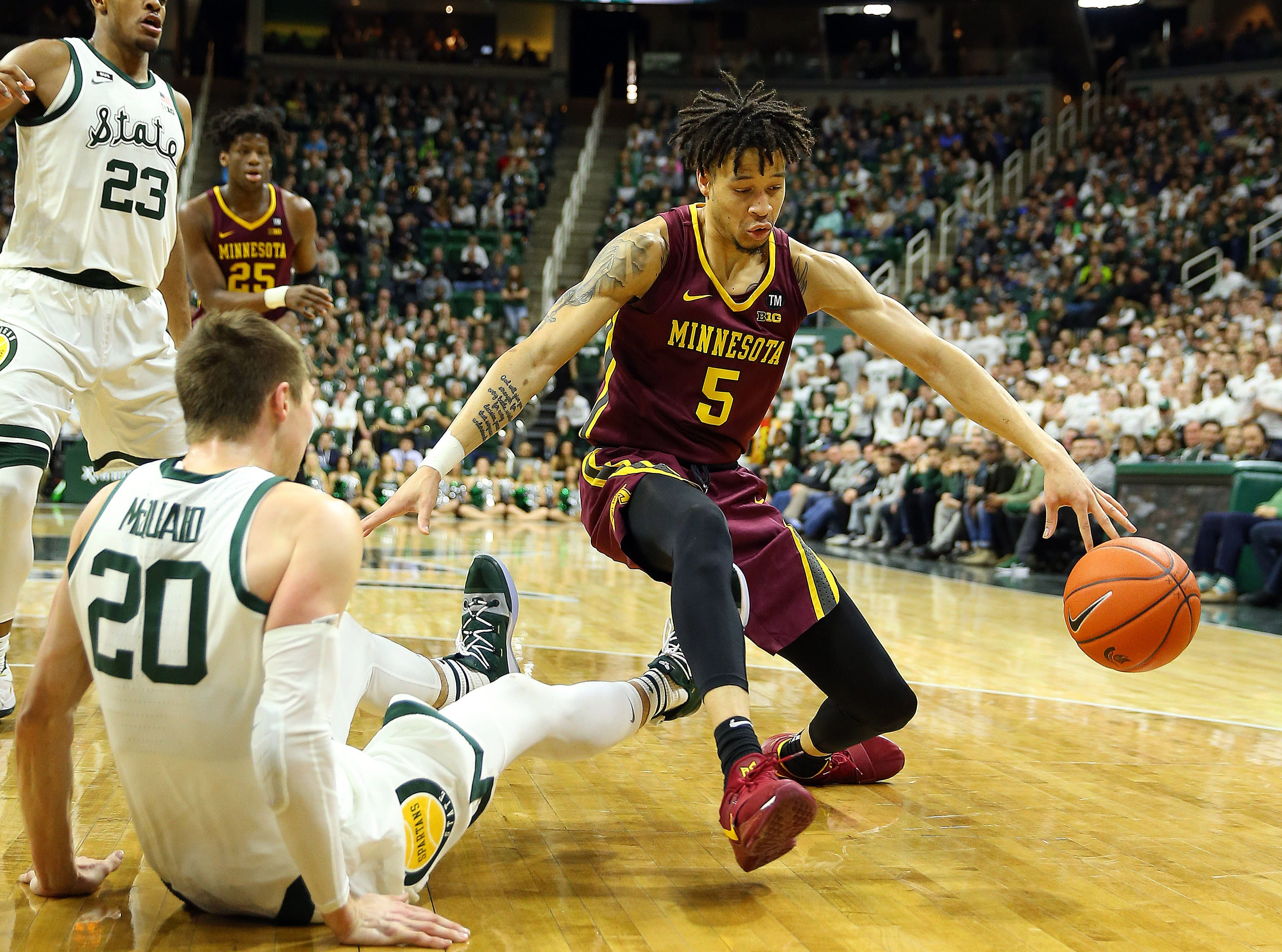 Feb 9, 2019; East Lansing, MI, USA; Michigan State Spartans guard Matt McQuaid (20) takes a charge against Minnesota Golden Gophers guard Amir Coffey (5) during the first half at the Breslin Center. Mandatory Credit: Mike Carter-USA TODAY Sports
