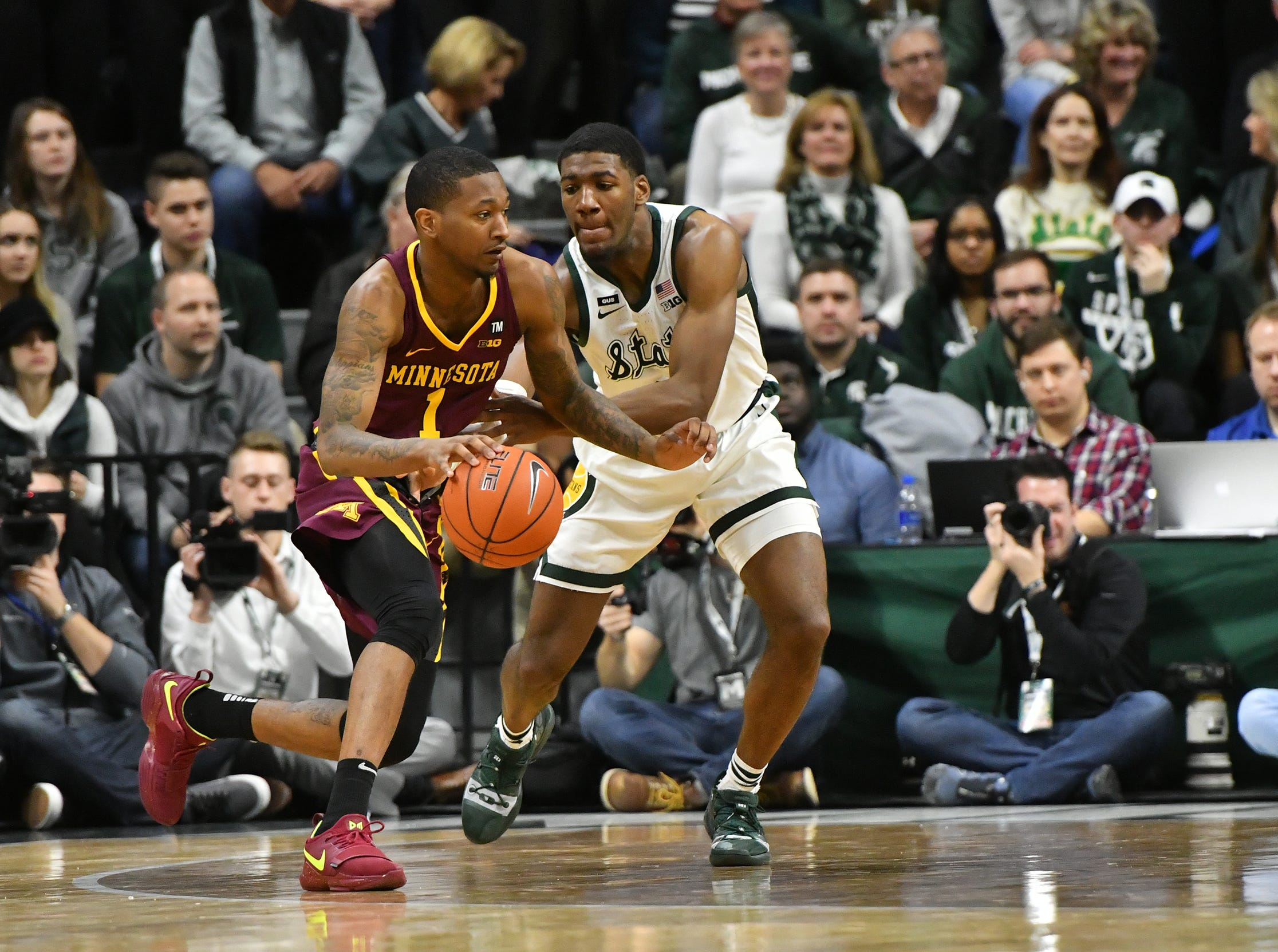 MSU forward Aaron Henry (11) guards Minnesota's Dupree Mc Brayer (1) in a Big Ten match-up Saturday, Feb. 9, 2019. MSU won 79-55.