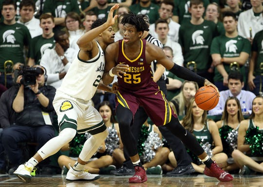 Feb 9, 2019; East Lansing, MI, USA; Minnesota Golden Gophers center Daniel Oturu (25) controls the ball against Michigan State Spartans forward Xavier Tillman (23) during the first half at the Breslin Center. Mandatory Credit: Mike Carter-USA TODAY Sports